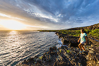 At sunset, a woman hikes along the historic 1871 Trail in Honanau, Big Island. The ancient trail was the main artery for coastal travel between several villages in the area.