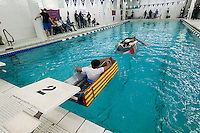 "Hundreds of students from Brooklyn Technical High School take part in the Cardboard Boat Regatta in the school's pool in Brooklyn in New York on Friday, March 1, 2013. As part of Engineering Week the teams of students constructed boats made only of cardboard and duct tape. The team's assigned ""captain"" piloted their boat from one end of the pool to the other and back in a heat with other boats, hopefully without sinking. The surviving boats were timed and the winners received bragging rights with an award also going to the most spectacular sinking. (© Richard B. Levine)"