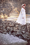A young bride with red hair alone wearing a wedding dress walks across a rock bridge