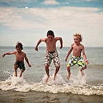 3 boys jumping in the water during summer at the beach