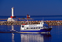A SHEPLER'S FERRY BOAT ENTERS THE MACKINAC ISLAND HARBOR WITH A BREAKWATER LIGHT AND THE ROUND ISLAND LIGHTHOUSE IN BACKGROUND.