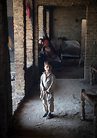 A boy and his family, refugees from Swat district, shelter in a derelict house in neighbouring Swabi district. The Pakistani government began an offensive against the Taliban in the Swat Valley in April 2009, which led to a major humanitarian crisis. Up to two million civilians were estimated to have been displaced by the fighting.