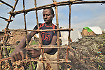 Mirenge Bulabyababene, displaced by war in the eastern Congo, builds a hut in a displaced persons camp set up on a lava flow in the village of Nzulu. A quarter of a million people have been newly displaced by fighting in the eastern Congo, where some 5.4 million have died since 1998 from war-related violence, hunger and disease.
