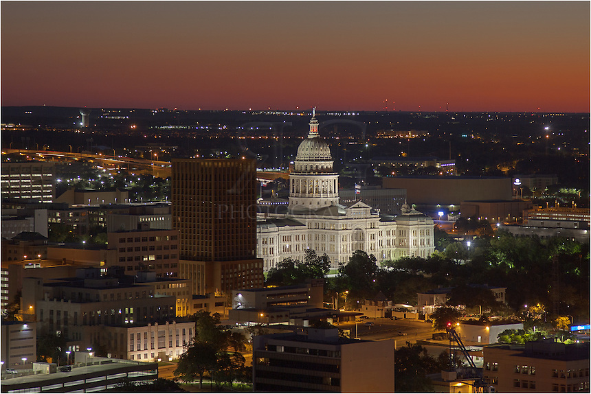About 25 minutes before sunrise on a clear, crisp morning, the eastern sky will turn a beautiful orange as the first light of day begins to lighten the atmosphere. Here, the sky begins to change in this vantage point showing the Texas State Capitol from a building located within the Austin skyline.