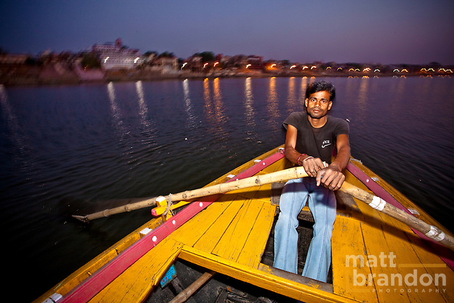 A young man rows a boat along the Ganges River early in the morning. The city of Varanasi, India is in the background.