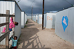 "CAPE TOWN, SOUTH AFRICA - MAY 3: Children play among tin houses on May 3, 2010, in Blikkiesdorp about 40 kilometers south of Cape Town, South Africa. Blikkiesdorp, which is Afrikaans for ""Tin Can Town"", was given its name by its residents because of the row-upon-row of tin-like shacks made of corrugated iron. It was built by the City of Cape Town in 1997 and about 1600 one-roomed shacks were built. It has been known for its bad conditions and a dumping ground for shack dwellers from other areas around Cape Town. Recently many street people in Cape Town has been forcefully removed and relocated to this place. The ones that have refused has been put in holdings cells or prisons such as Pollsmoor Prison. This campaign has identified in the preparation for the soccer World Cup, who starts on June 11, 2010 and goes on for a month. The City of Cape Town doesn't want international visitors to be hassled by street people. (Photo by Per-Anders Pettersson)"