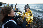A volunteer wraps an insulating blanket around a cold and wet refugee boy on a beach near Molyvos, on the Greek island of Lesbos, on November 2, 2015. The boy and his family were received by local and international volunteers, then proceeded on their way toward western Europe. The boat was provided by Turkish traffickers to whom the refugees paid huge sums to arrive in Greece.