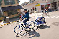 An adult pulls children in a buggy while biking on Mackinac Island in Michigan.