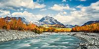 Sun breaking it's way through clouds to light up autumn colors on Granite Creek on Gelnn Highway Alaska