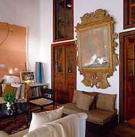 A massive antique mirror takes up the whole wall between a pair of double doors in the living room