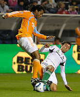 Chicago midfielder Baggio Husidic (9) slide tackles the ball away from Houston's Adrian Serioux (51).  The Chicago Fire defeated the Houston Dynamo 2-0 at Toyota Park in Bridgeview, IL on April 24, 2010.
