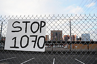 "Phoenix, Arizona. September 22, 2012 - A ""Stop SB 1070"" poster hanged on a fence at the ""Festival of Resistance"" was held, seeks to inspire undocumented immigrants to show resistance to SB 1070, Arizona's ""Show Me Your Papers,"" law. City of Phoenix' skyline is seen in the background. Photo by Eduardo Barraza © 2012"