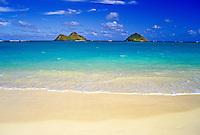 Mokulua Islands with blue sky, blue-green waters, sandy beach and gentle waves from Lanikai beach.