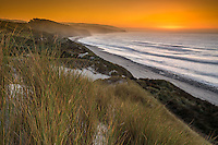 Intense sunset over remote coastline with sand dunes and marram grass near Paturau on west coast of South Island, Nelson Region, New Zealand