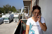 Italy. Lazio region. Capena. Cornelia Mihaelu is a romanian citizen and has lived in Italy for the last 10 years. She talks on the phone while standing on her flat's balcony. She wears a white t-shirt with a soldier carrying a weapon and the words revolution. Romanian immigration. Capena (until 1933 called Leprignano) is a town and comune in the province of Rome. 2509.2011 © 2011 Didier Ruef