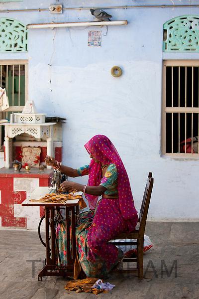 Indian woman wearing traditional Rajasthani sari works at home using sewing machine in village of Nimaj, Rajasthan, Northern India