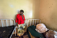 Africa, N. Uganda, Gulu. With so few resources to address mental health in developing countries the care usually falls to the family members.  The process is often traumatic and frightening for caretakers when they have to bring their distressed loved ones in to be evaluated by a healthcare professional. This man was brought to the local mental health clinic by his wife and brother to be evaluated and was so violent that he had to be sedated. His wife holds the ropes that were used to restrain him and weeps from the sheer exhaustion of the experience.
