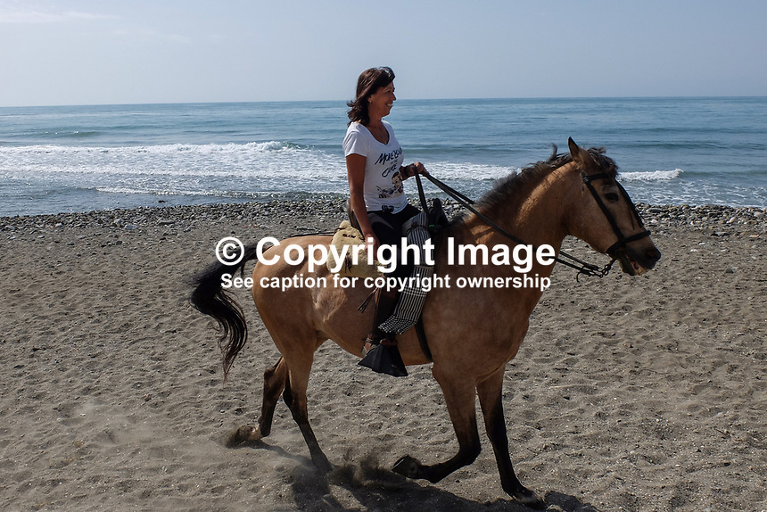 Horsewoman has a leisurely Sunday morning canter along the shore between Puerto Banus and San Pedro de Alcantara. April, 2017, 201704233487<br /><br />Copyright Image from Victor Patterson, 54 Dorchester Park, <br />Belfast, UK, BT9 6RJ<br /><br />t1: +44 28 9066 1296 (from Rep of Ireland 048 9066 1296)<br />t2: +44 28 9002 2446 (from Rep of Ireland 048 9002 2446)<br />m: +44 7802 353836<br /><br />e1: victorpatterson@me.com<br />e2: victorpatterson@gmail.com<br /><br />www.victorpatterson.com<br /><br />Please see my Terms and Conditions of Use at www.victorpatterson.com. It is IMPORTANT that you familiarise yourself with them.<br /><br />Images used on the Internet must be visibly watermarked i.e. &copy; Victor Patterson within the body of the image and copyright metadata must not be deleted. Images used on the Internet have a size restriction of 4kbs and will be chargeable at current NUJ rates unless agreed otherwise.<br /><br />This image is only available for the use of the download recipient i.e. television station, newspaper, magazine, book publisher, etc, and must not be passed on to any third party. It is also downloaded on condition that each and every usage is notified within 7 days to victorpatterson@me.com<br /><br />The right of Victor Patterson to be identified as the author is asserted in accordance with The Copyright Designs And Patents Act (1988).