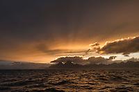 Rays of sunlight over Vågakallen mountain peak, Lofoten Islands, Norway