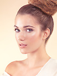 Beauty portrait of a young woman with light natural look and her hair in updo isolated on beige background