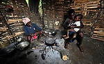 Jean Manuel Dupres (left), 13, cooks his family's daily meal while his brother Nigenson, 15, holds their younger brother Jefte in their home in Despagne, a rural village in southern Haiti where the Lutheran World Federation has been working with residents to improve their quality of life.