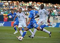 El Salvador's Arturo Alvarez shoots and scores in front of Cuba's Hanier Dranguet (2) and Carlos Domingo Francisco (2).  El Salvador defeated Cuba 6-1 at the 2011 CONCACAF Gold Cup at Soldier Field in Chicago, IL on June 12, 2011.