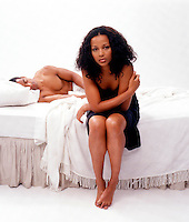 African American woman on edge of bed with man in background