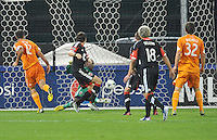 Will Bruin (12) of the Houston Dynamo scores against Bill Hamid (28) of D.C. United in the minute 78th of the game. The Houston Dynamo defeated D.C. United 4-0, at RFK Stadium, Wednesday May 8 , 2013.
