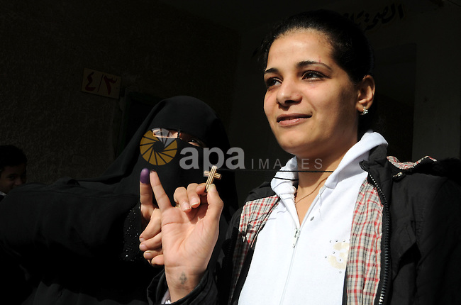 An Egyptian Christian near veiled Egyptian woman shows her ink-stained finger holding a cross after voting at a polling station in Qaliubia, some 40 kms north of Cairo, on January 4, 2012 as Egyptians headed to the polls again in the final round of a phased election to choose the first parliament since a popular uprising toppled Hosni Mubarak in February. Photo by Ahmed Asad