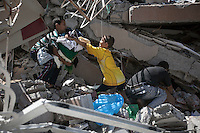 "August 24, 2014 - Gaza City, Gaza strip, Palestinian Territory: Palestinian residents climb to the rubble of an apartment complex buildiing as they collect their belongings after it was targeted by an airstrike raid last night in Al-Zawayda neighborhood of central Gaza City as ""Protective Edge"" Israeli military operation continues in the Gaza strip. (Narciso Contreras/Polaris)"