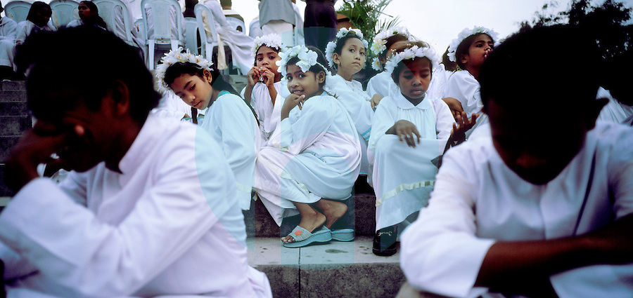 December 13th 2003-Dili, Timor-Leste-Young girls dressed as angles, take a rest, while participating in a religious ceremony celebrating the Virgin Marry in the Bidau Lecedere area of Dili.  Photograph by Daniel J. Groshong/Tayo Photo Group