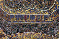 Detail of kufic script and vegetal motifs in tesserae (glass mosaic with gold or coloured backing), in the dome above the maqsura, a richly decorated ribbed vault with small dome in front of the mihrab, redecorated under Al-Hakam II in 961, in the Cathedral-Great Mosque of Cordoba, in Cordoba, Andalusia, Southern Spain. The ceiling is decorated with kufic script, floral motifs, and a sunburst radiating from a tiny central star, with light coming from 8 latticed side windows. The first church built here by the Visigoths in the 7th century was split in half by the Moors, becoming half church, half mosque. In 784, the Great Mosque of Cordoba was begun in its place and developed over 200 years, but in 1236 it was converted into a catholic church, with a Renaissance cathedral nave built in the 16th century. The historic centre of Cordoba is listed as a UNESCO World Heritage Site. Picture by Manuel Cohen