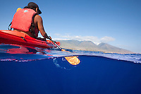 A young man paddling a kayak off the coast of Maui.