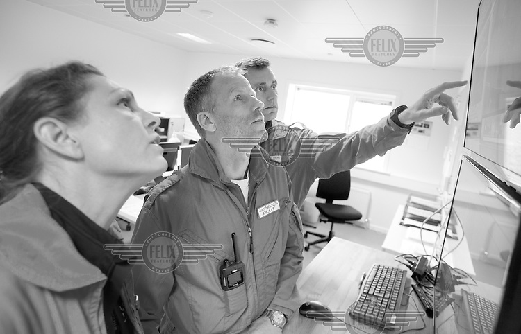 Crew study weather and maps prior to a mission.  Denmarks first  air ambulance serivce, operated by Norwegian Air Ambulance. The crew is pilot Jan Nielsen, HEMS paramedic Lars Greve-Wilms and doctor Rikke Helene Rasmussen. <br /> <br /> The crew operate an Airbus EC-135 out of the Ringsted base, one of three bases in Denmark.