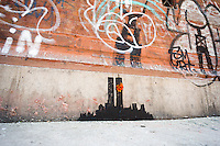 "Street art enthusiasts flock to the Tribeca neighborhood of New York on Tuesday, October 15, 2013 to see the fifteenth installment of Banksy's graffiti art, ""Tribecca"". The elusive street artist is creating works around the city each day during the month of October and this installment shows a silhouette of the World Trade Center with a flower attached.  (© Richard B. Levine)"