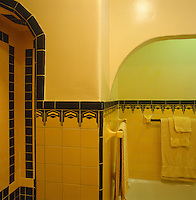 An Art Deco motif borders the wall tiles in this period bathroom