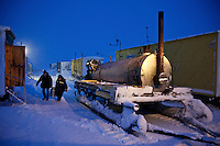 Men, working at a camp set up by oil and gas prospecting company Siesmorevzedka in the Arctic tundra, deliever hot water to dormatories. The water is heated in the large diesel powered tank to their left. /Felix Features