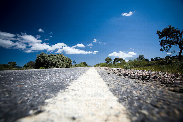 Low level shot of a white road line, province of Caceres, Spain. With blue sky and small clouds
