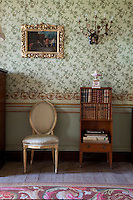 The elaborate green and gold floral wallpaper in the drawing room was hung in the 1820s and complements the gilt frames of the many paintings displayed in the room