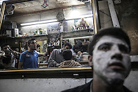 At the evening time a group of man await for their turn as another ones get different services at one of the numerous barber shops in downtown Manbij, located at the northeast of Aleppo province. .
