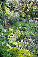 A well-stocked, lush garden with a table and chair on the lawn. The various flowers and shrubs provide a contrasting variety of shapes, textures and greens.