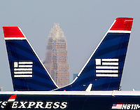 US Airways express jets sit at the gates, with the Bank of America corporate tower in the background, at Charlotte-Douglas International Airport in Charlotte, North Carolina. Charlotte-based photographer has other images of transportation, airplanes on runways (and taking off and landing) and interior/exterior airport images of Charlotte-Douglas Intl Airport in portfolio.