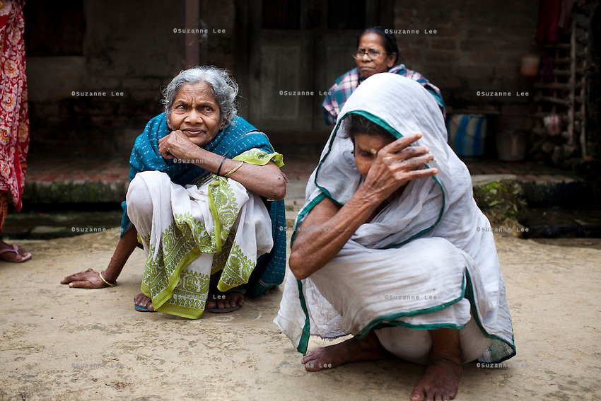 """(L-R: (blue) Saraswati Saha, 84; unnamed; and (white) Kamla Das, 90) Three elderly women who were the original refugees of The Partition recall being brought to Cooper's Camp on trains and trucks as they gather outside their homes in Cooper's Camp, Nadia district, Ranaghat, North 24 Parganas, West Bengal, India, on 19th January, 2012. """"The government will neither eat us nor spit us out."""" says Kamla Das. """"They dropped us off here (in 1947) and I'm still here!"""" Over 60 years after the bloody creation of Bangladesh in 1947, refugees who fled what was then known as West Pakistan to India still live as refugees, raising their children as refugees, and standing in line for government handouts..Photo by Suzanne Lee"""