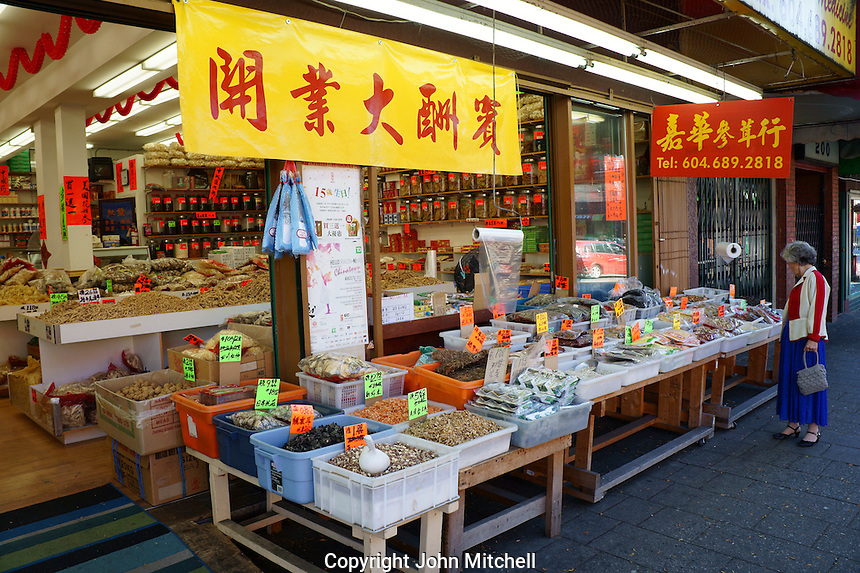 Elderly Chinese  woman shopping at a food and herb  shop in Chinatown, Vancouver, British Columbia, Canada