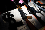 "Uzi submachine guns, AK-47s, M-4 assault rifles and other automatic firearms at the Rocky Mountain Fifty Caliber Shooting Association's 2009 Machine Gun Shoot.  ..Each year the organization holds two sanctioned machine gun shoots during which machine gun owners and vendors bring their guns to shoot for a three day-long event.  Organizer Bob McBride described the muddy Fort Morgan event as ""machine gun Woodstock without the dope.""  The annual events draw shooters from around the world to shoot at propane tanks, cars filled with fuel, boxes of stick dynamite, and other ""reactive "" targets.  People wishing to own automatic firearms must be licensed by the federal government to purchase the weapon."