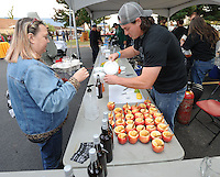 NWA Democrat-Gazette/ANDY SHUPE<br /> Michelle Smith of Springdale (left), a church member since 1985, speaks with Codie Bailey of Bella Vista as Saturday, Oct. 17, 2015, as he pours a sample of Pappy's Hard Cider during the second St. Raphael Catholic Church Brewtober Chilifest in Springdale. The event gave attendees the chance to taste home-brewed beers and ciders and sample chili with awards going to the two winners as determined by a popular vote.