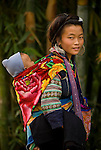 Mother carrying her son past bamboo backdrop in Tafen Village, Hill tribe town in Sa Pa region of Northern Vietnam