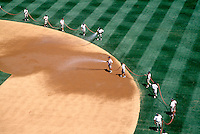 WORKERS WATERING A  BASEBALL STADIUM<br />