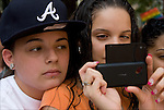 Hispanic American lesbian couple taking photos with cellphone in crowd during the Gay and Lesbian  Pride Parade in Greenwick Village
