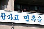 Students look out of a classroom as a banner written in Hangul hangs on an exterior wall of the Tokyo Korean High School in Tokyo, Japan on Thursday 07 October, 2010..Photographer: Robert Gilhooly